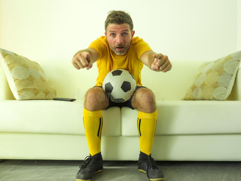 Funny portrait of young stressed and excited football fan man watching soccer game on TV at home couch dressed in team player stock photos