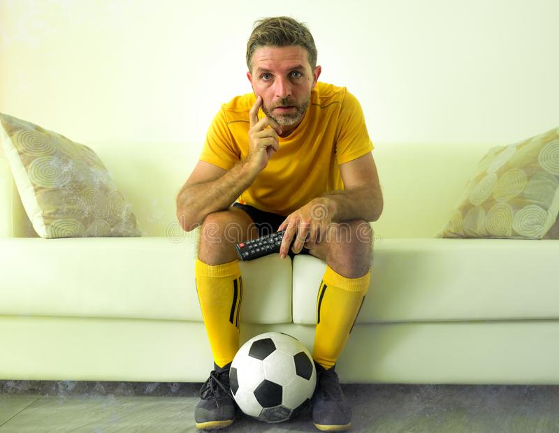Funny portrait of young stressed and excited football fan man watching soccer game on TV at home couch dressed in team player. Uniform feeling the stress and stock images