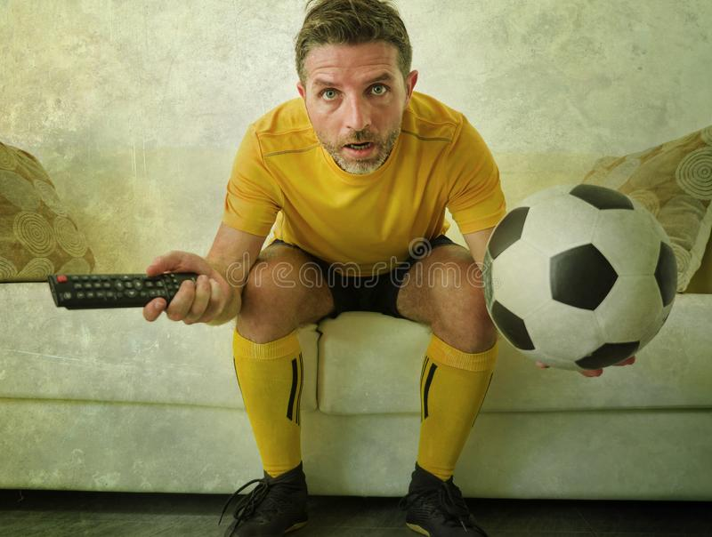 Funny portrait of young stressed and excited football fan man watching soccer game on TV at home couch dressed in team player. Uniform feeling the stress and royalty free stock image