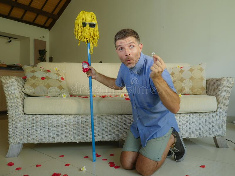 Funny portrait of young weird crazy and happy man holding mop with sunglasses as if it was his fiance kneeling and proposing marri royalty free stock image