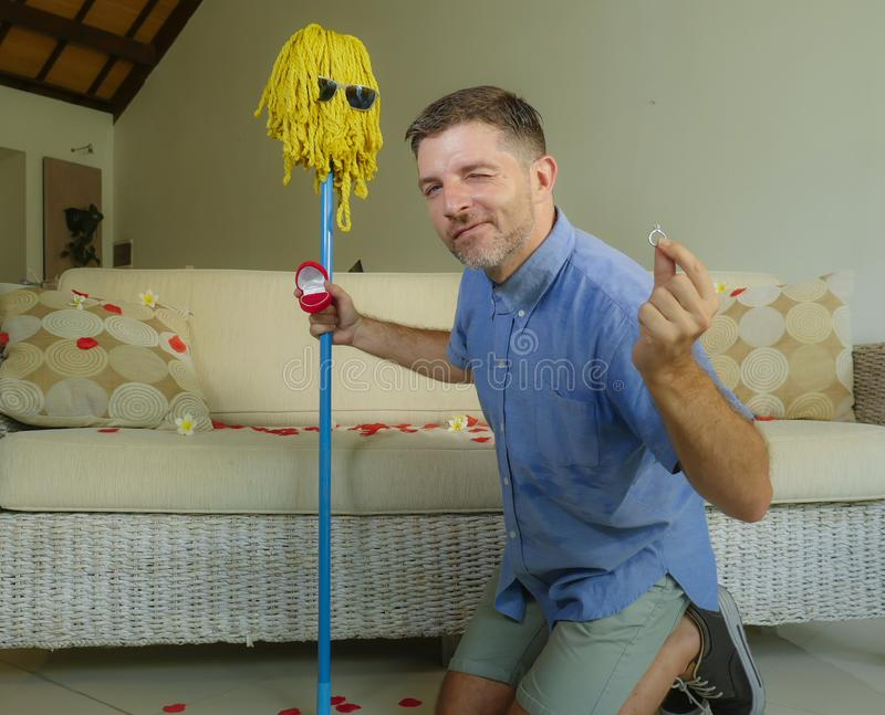 Funny portrait of young weird crazy and happy man holding mop with sunglasses as if it was his fiance kneeling and proposing marri royalty free stock photo