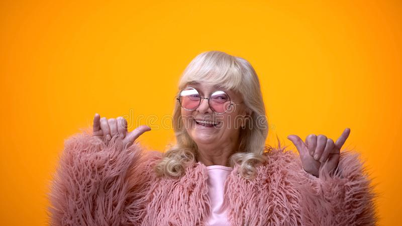 Funny positive elderly female in pink coat making rocker gesture, having fun stock photography