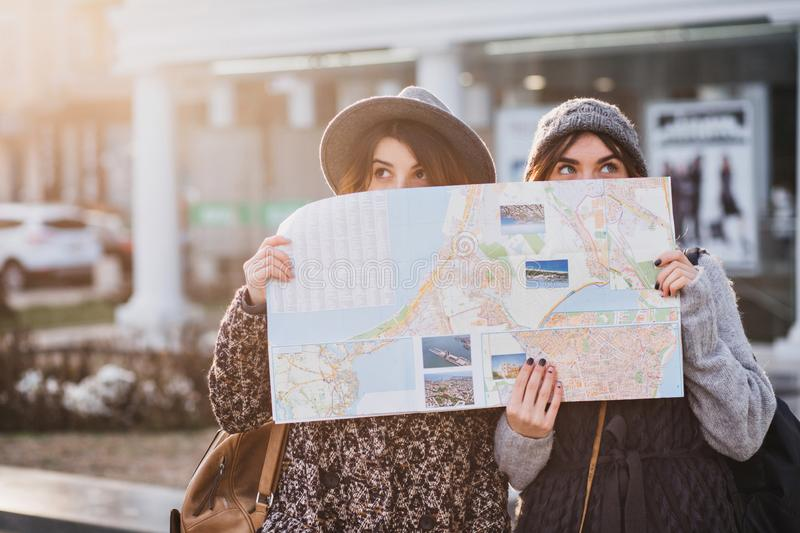 Funny positive image of fashionable girls on sunny street having fun in city, hiding behind the citymap. Travelling. Together, best friends, get a lost in big stock photography