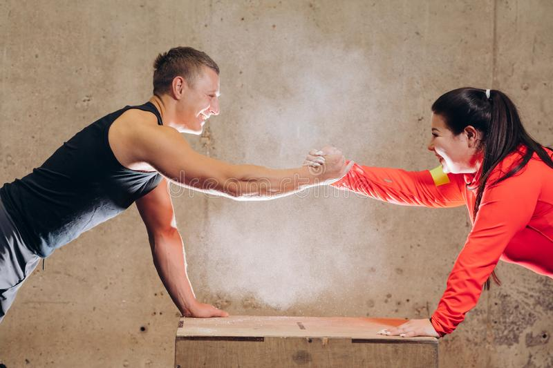 Funny positive obese woman ahd sporty man handshaking. Funny positive obese women ahd sporty men handshaking while doing exercises on the wooden box. close up stock photo