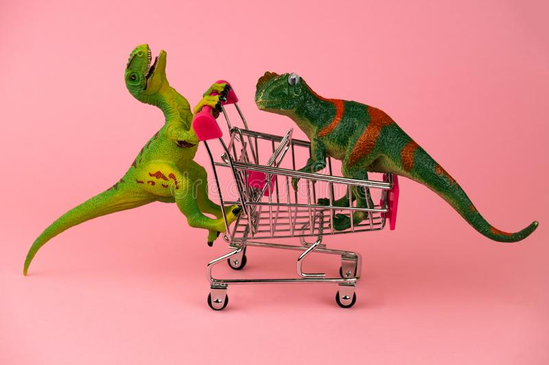 Dinosaurs rolling each other in shopping carts on soft pink background. Funny postcard with dinosaurs rolling each other in shopping carts on soft pink stock images