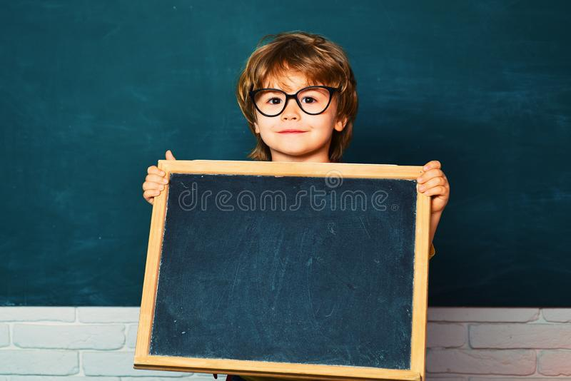 Funny pupil. Elementary school and education. Preschooler. Blackboard copy space. Little children at school lesson royalty free stock photos