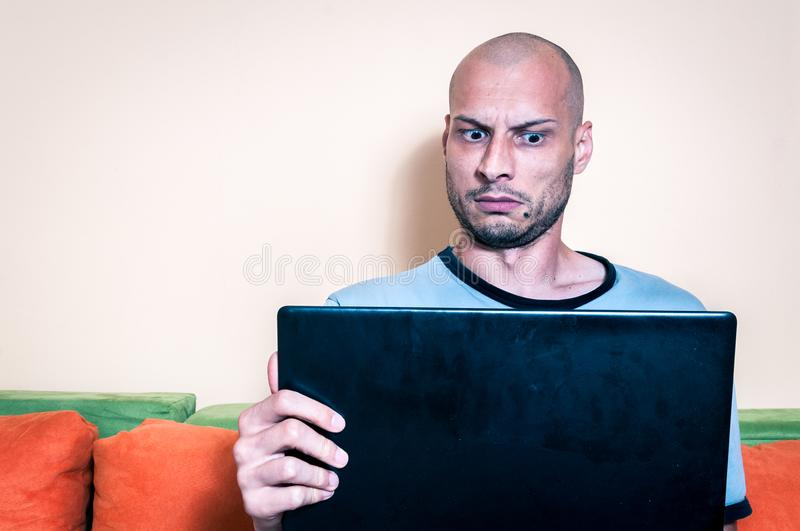 Funny reaction and facial expression of the man who find out online inappropriate content in the pop up message on his laptop comp. Uter royalty free stock photo