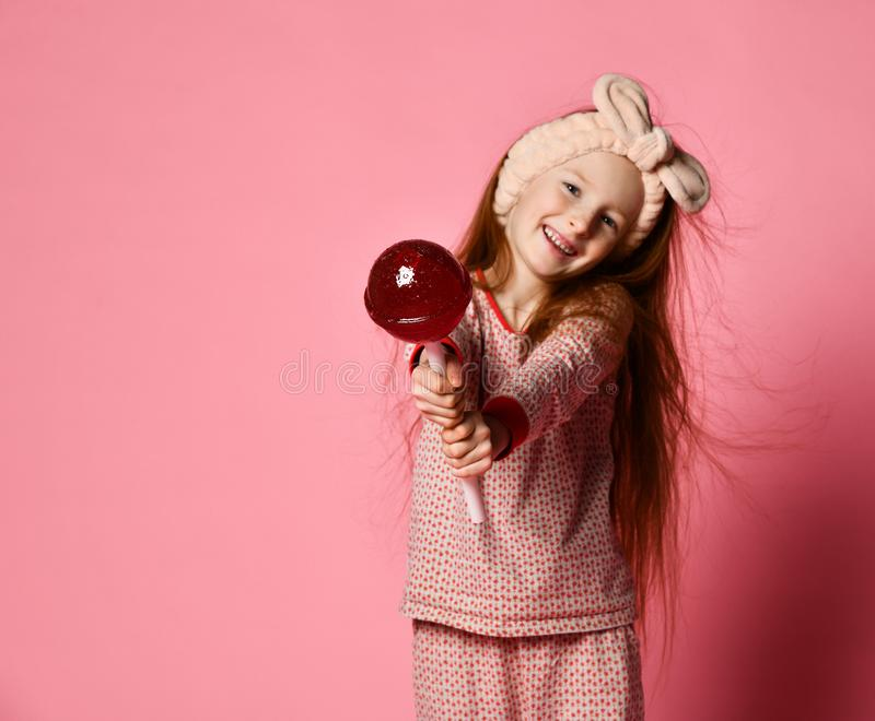 Funny child with candy lollipop, happy little girl eating big sugar lollipop royalty free stock photography