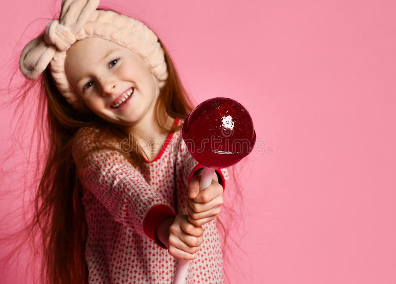 Funny child with candy lollipop, happy little girl eating big sugar lollipop stock photo