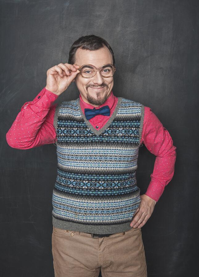 Funny retro style teacher in eyeglasses looking at you on blackboard royalty free stock photos