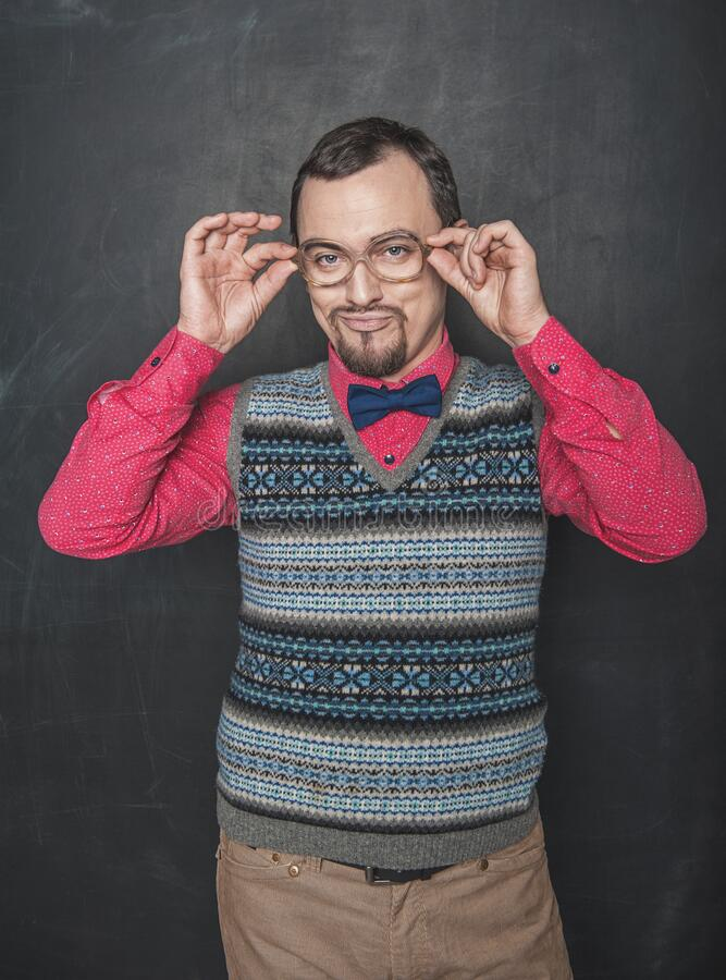 Funny retro style teacher in eyeglasses looking at you on blackboard stock image