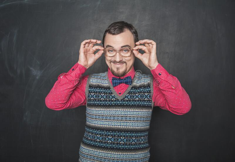 Funny retro style teacher in eyeglasses looking at you on blackboard stock photo