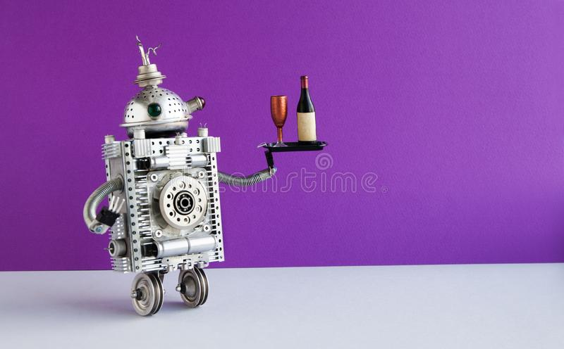 Funny robot waiter serving a tray with a bottle and wine glass. Two wheels domestic robotic character on violet wall stock images