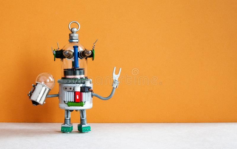 Funny robotic toy holds light bulb. creative design futuristic humanoid robot on brown gray background. copy space.  royalty free stock photos
