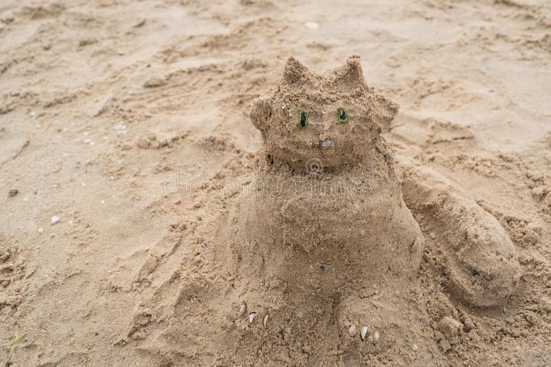 Funny sand sculpture of a cat on the beach. Summer holidays.  royalty free stock photography