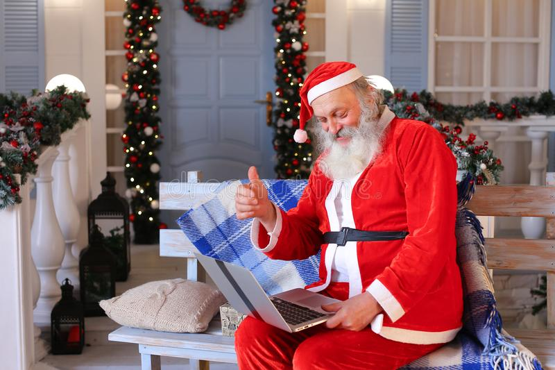 Funny Santa Claus showing thumbs up and working with laptop. Happy Father Christmas using approving gestures and enjoying with laptop. Cozy room with royalty free stock images