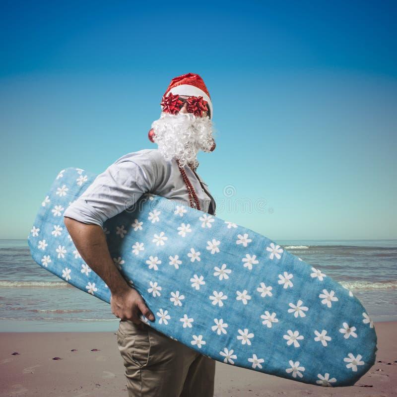 Funny santa claus surfer beach royalty free stock photography