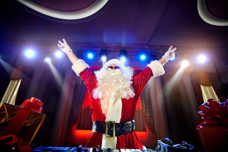 Funny Santa DJ mixes in the beams of light music. royalty free stock images