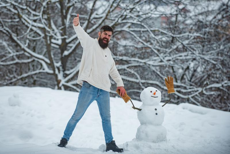 Funny Santa man posing on winter weather. Joyful Handsome young hipster Having Fun with snowman in Winter Park. Merry stock photo