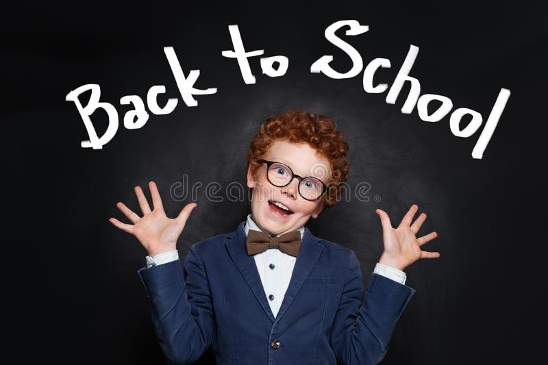 Funny scared child boy on blackboard background. Back to school concept stock images