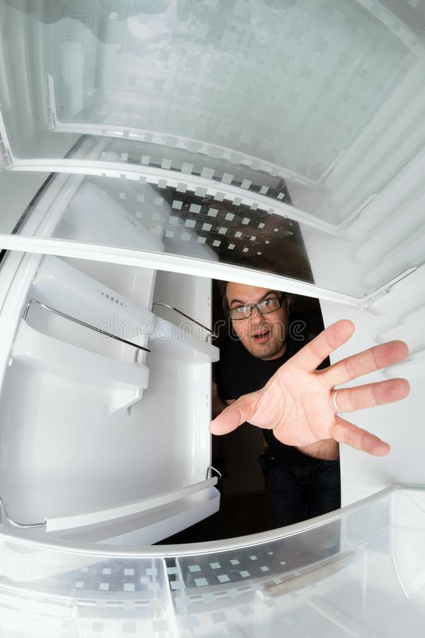 Funny scene of hungry young man opening the door of the fridge. And reaching for food, view from inside the freezer stock photos