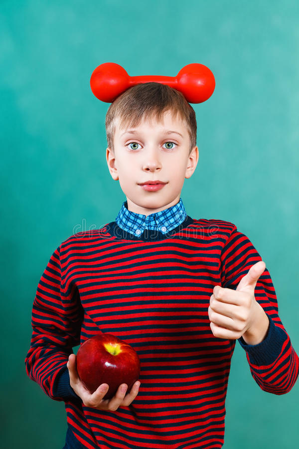 Funny schoolboy with red dumbbell and apple showing thumbs up stock photos