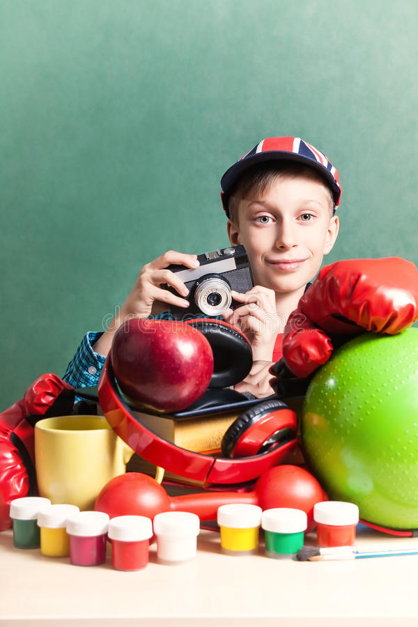 Funny schoolboy sitting at table with colorful school accessories stock photography