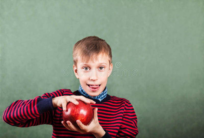 Funny schoolboy standing over a blackboard holding a big red apple stock photography