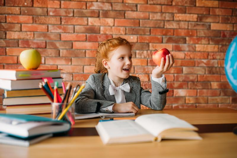 Funny schoolgirl with apple sitting at the table royalty free stock photography