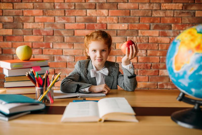 Funny schoolgirl with apple sitting at the table stock photos