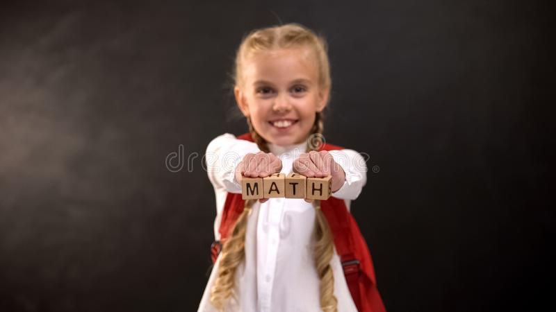 Funny schoolgirl showing wooden cubes with math word, exact sciences lesson stock photos