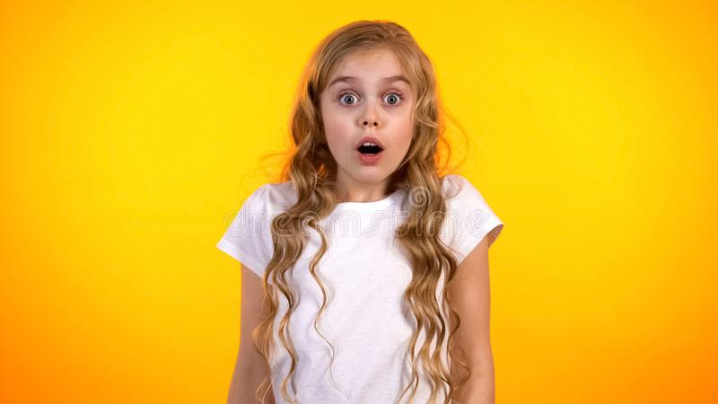 Funny schoolgirl with widely opened eyes looking to cam, shocking news, promo stock photography