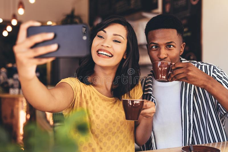 Funny selfie at cafe. Woman taking selfie with friend making funny expressions while drinking coffee. Friends taking selfie with smart phone at cafe stock photography