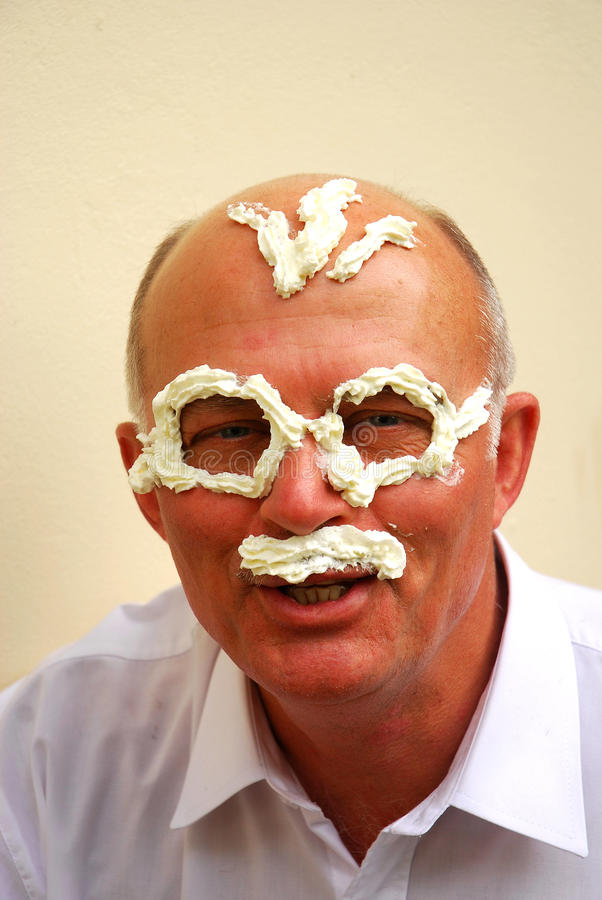Funny senior. Head portrait of a funny Caucasian senior man with smiling facial expression and whipped dairy cream in his face forming eyeglasses, hair and a