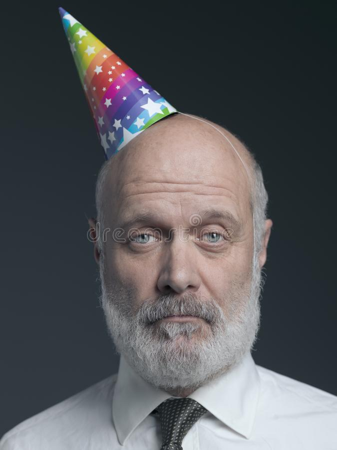 Funny senior bald man with party hat stock images