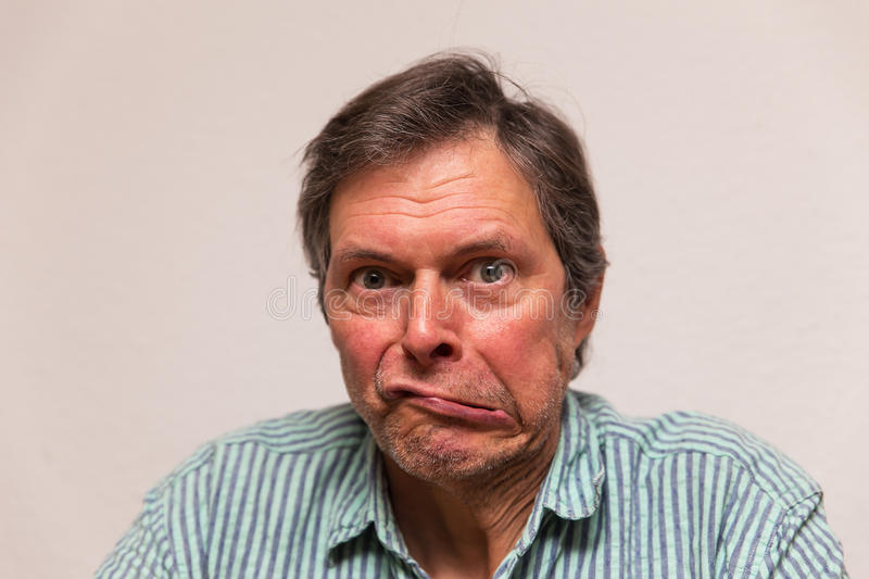 Funny senior making a grimace. Funny senior citizen is making a grimace royalty free stock photo