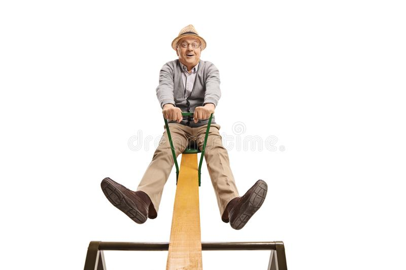 Funny senior man sitting on a seesaw stock image