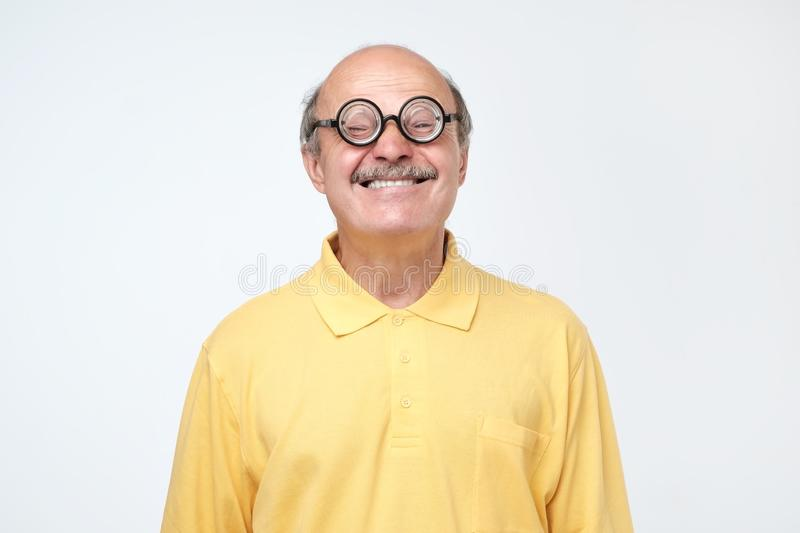 Funny senior man wearing stupid glasses looking at camera. Portrait of a funny senior man wearing stupid glasses looking at camera over gray background stock photos