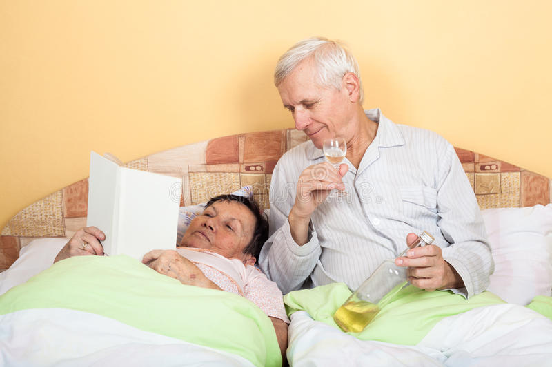 Funny seniors relax with alcohol in bed. Funny senior men drinking alcohol and women reading book in bed royalty free stock photos