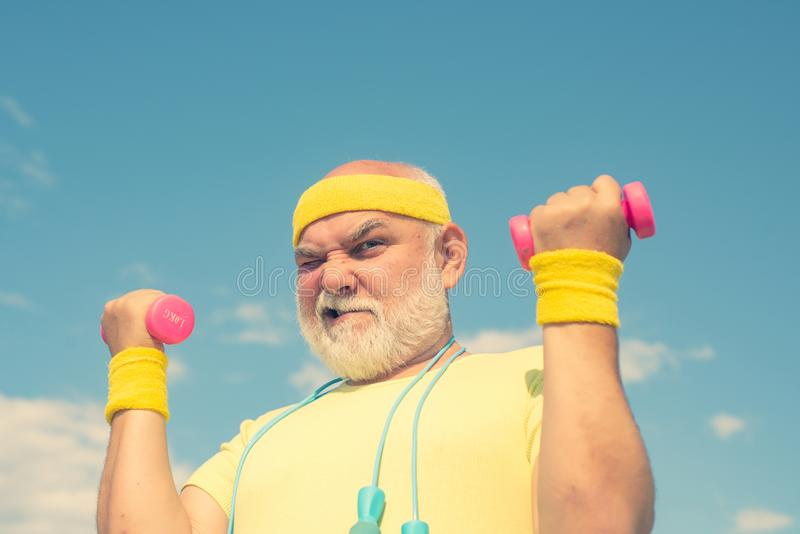 Funny Senior sportman exercising with lifting dumbbell on blue sky background. Isolated, copy space. Happy Senior sportman exercising with lifting dumbbell on stock photo