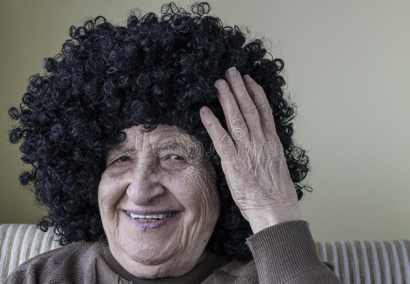 Funny senior woman wearing curly black wig royalty free stock image