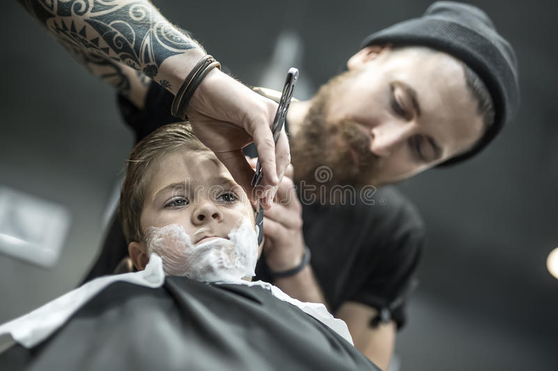 Funny shaving of little boy. Little kid with a shaving foam on the face in the barbershop. He wears a black salon cape. Bearded barber with a tattoo is shaving stock images