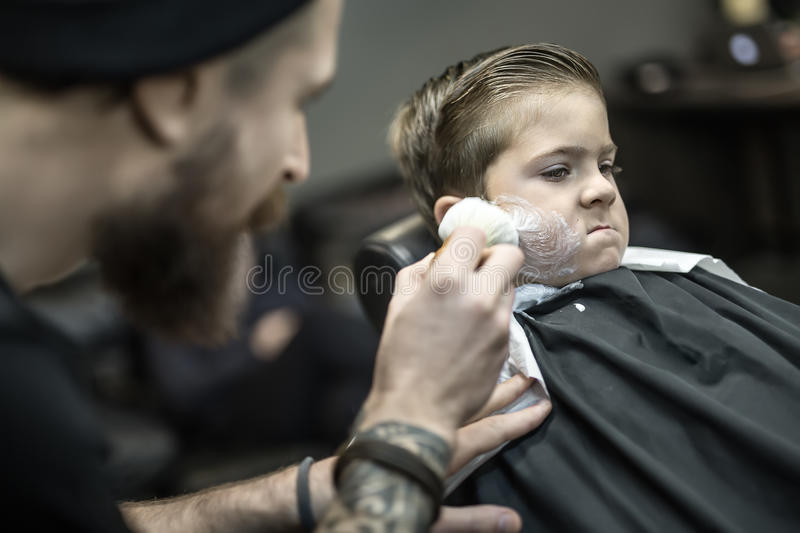 Funny shaving of little boy. Positive kid in a black salon cape in the barbershop. Bearded barber with a tattoo applies shaving foam with the help of the shaving stock photography