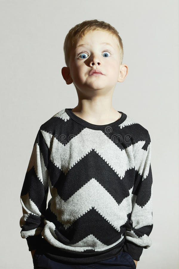 Funny shock face child in sweater.children trend.little boy.emotion stock photography