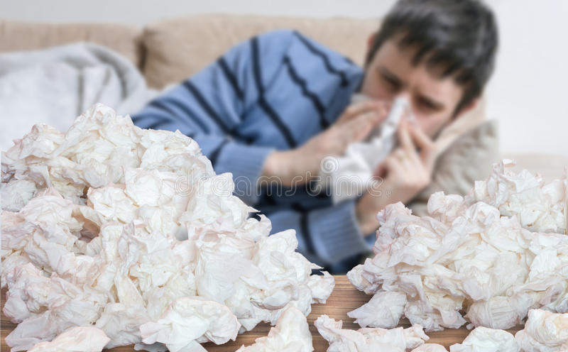 Funny sick man who has flu or cold is blowing his nose. Pile of tissues in front royalty free stock photo