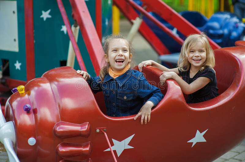Funny sisters on carousel ride. Two funny sisters on carousel ride in red airplane in children's park royalty free stock image