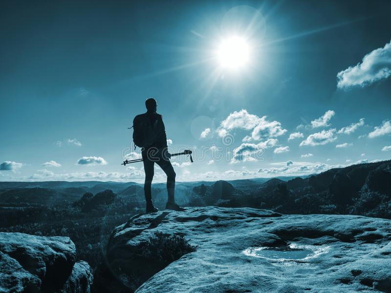 Funny slim tourist guy with backpack holds trekking stick stock images