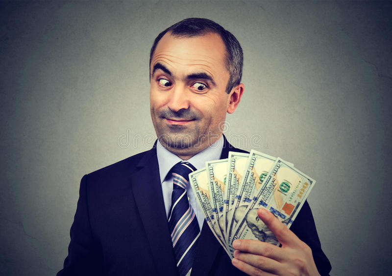 Funny sly business man holding looking at money dollar banknotes stock photography
