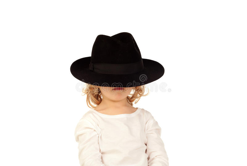 Funny small blond child with black hat. Isolated on a white background royalty free stock photography