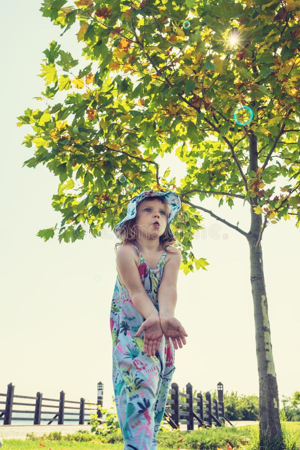 Funny small girl catches soap bubbles and having fun in park royalty free stock photography